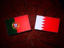 Португалки сигнализируют с бахрейнским флагом на пне дерева Стоковое Фото