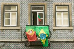 Португалки и бразильские флаги показаны от балкона квартиры в Лиссабоне, Лиссабоне, Португалии, в поддержку футбола кубка мира стоковое фото rf