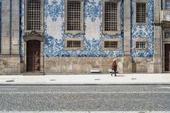Порту, Португалия - 4-ое апреля 2017: Женщина идя перед крыть черепицей черепицей фасадом Igreja делает Carmo в p стоковое фото rf