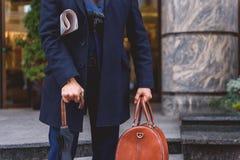 Портфель и бумага нося бизнесмена в городе Стоковое фото RF