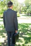 Портфель нося бизнесмена в парке Стоковое фото RF