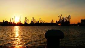 Порт груза вытягивает шею силуэт на заходе солнца Стоковые Фотографии RF