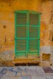 ПОРТ D ANDRATX, ИСПАНИЯ - 18-ОЕ АВГУСТА 2017: Красивый вид малой старой зеленой двери в поврежденной стене, в городке порта d And Стоковые Изображения RF