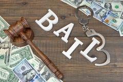 ПОРУКА молотка, знака, наручники и наличные деньги доллара на деревянной предпосылке Стоковое Изображение