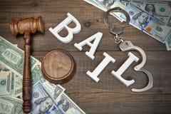 ПОРУКА молотка, знака, наручники и наличные деньги доллара на деревянной предпосылке Стоковое фото RF