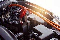 Поручая автомобиль батареи на расплывчатой предпосылке Ener перезарядки метафоры Стоковое фото RF