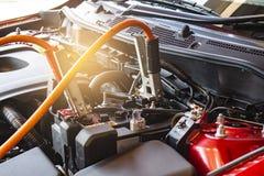 Поручая автомобиль батареи на расплывчатой предпосылке Ener перезарядки метафоры Стоковые Изображения RF