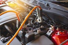 Поручая автомобиль батареи на расплывчатой предпосылке Ener перезарядки метафоры Стоковое Изображение RF