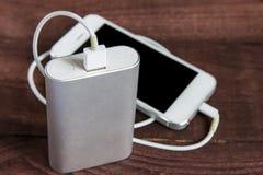 Поручая Smartphone с серым портативным внешним powerb батареи Стоковое Изображение RF