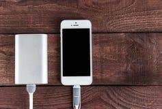 Поручая Smartphone с Powerbank на деревянном столе Портативно стоковое фото rf
