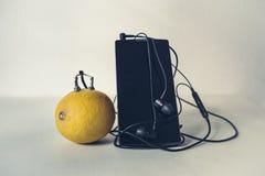 Поручите мобильный телефон используя лимон стоковые изображения rf