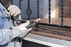 Поручни металла заварки работника на лестницах Украина Стоковая Фотография