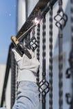 Поручни металла заварки работника на лестницах Украина Стоковое Фото