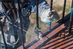 Поручни металла заварки работника на лестницах Украина Стоковое фото RF