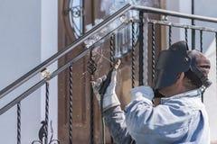 Поручни металла заварки работника на лестницах Украина Стоковые Фотографии RF