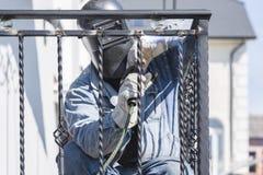 Поручни металла заварки работника на лестницах Украина Стоковое Изображение