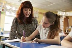Порция учителя начальной школы с classwork на столе ½ s ¿ girlï стоковое фото