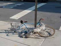 Порченный велосипед обернутый в отбросе сломанном на угле улицы стоковое фото rf