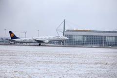 Посадка Люфтганзы CityLine Embraer ERJ-195 D-AEMD в авиапорте Мюнхена Стоковая Фотография