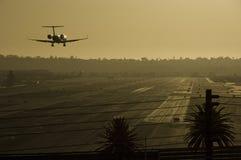 Посадка самолета на заходе солнца. стоковое фото