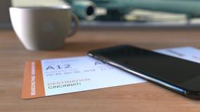 Посадочный талон к Цинциннати и smartphone на таблице в авиапорте пока путешествующ к Соединенным Штатам акции видеоматериалы