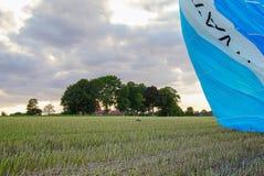 Посадка воздушного шара горячего воздуха в зеленом поле Стоковые Изображения