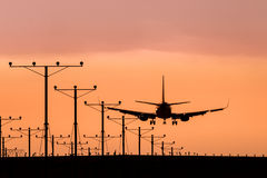 Посадка самолета двигателя на заходе солнца Стоковые Изображения RF
