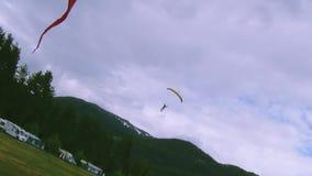 Посадка Skydiver на зеленом поле среди леса, гор пристаньте празднество к берегу fanoe Дании дня летая желтый цвет высокого неба  сток-видео