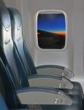 Посадочные места и окно внутри воздушного судна с взглядом крыла и солнец Стоковая Фотография