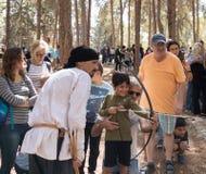 Посетители ` деревни Викинга ` реконструкции учат снять стрелку в лесе около Бен Shemen в Израиле стоковая фотография