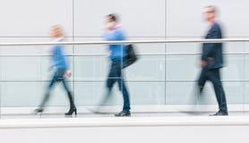 Посетители торговой ярмарки идя в чистый футуристический коридор Стоковое фото RF