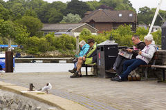 Посетители к курорту на море Lymington ослабляют на деревянных скамьях гаванью на тускловатый холодный день стоковые фото
