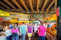 Посетители просматривают стойлы на BoroughMarket, одном из самых больших и самых старых рынков в городе, конструированном в 1800s Стоковое Изображение