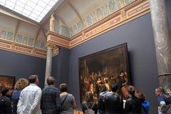 Посетители смотря известную ночной дозор Рембрандтом на t Стоковое Изображение