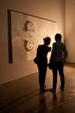 2 посетителя восхищая или обсуждая часть искусства Стоковое Фото