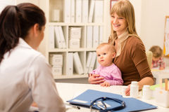 посещение педиатра мати проверки младенца поднимающее вверх Стоковое фото RF