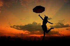 поскачите женщина зонтика захода солнца силуэта стоковая фотография