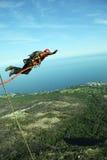 Поскачите с скалы с веревочкой Excited маленькая девочка стоковая фотография rf