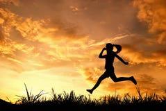 поскачите silhouetted ходом женщина захода солнца стоковые фото