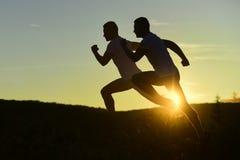 Последовательность мужских силуэтов бежать на предпосылке рассвета Стоковое фото RF