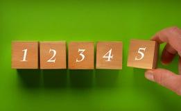 Последовательность номеров на деревянных кубах - зеленая предпосылка Стоковая Фотография