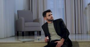 После бизнесмена работы тяжелого дня молодого сидя на поле и чувствуя расстроен и подавлен он хочет принимать некоторые таблетки сток-видео