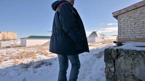 После мужского исследователя в джинсах и теплой формы идя через снег на день зимы солнечный между сток-видео