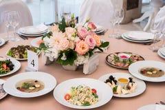 Послуженный для таблицы ресторана банкета со стеклами блюд, закуски, столового прибора, вина и воды, европейской едой, выборочным стоковые фотографии rf