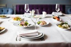 Послуженный для таблицы ресторана банкета со стеклами блюд, закуски, столового прибора, вина и воды, европейской едой, выборочным стоковое изображение rf