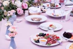Послуженный для таблицы ресторана банкета со стеклами блюд, закуски, столового прибора, вина и воды, европейской едой, выборочным стоковое фото rf