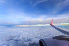 Посмотрите вне окно самолета См. белые группы облака и крыло самолета Стоковые Фото