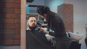 Посмотрите женских отрезков парикмахера волосы бороды мужского клиента 4K акции видеоматериалы