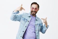 Посмотрите меня, я холодный папа Портрет красивого взрослого бородатого мужчины в ультрамодных солнечных очках и куртке джинсовой стоковое фото
