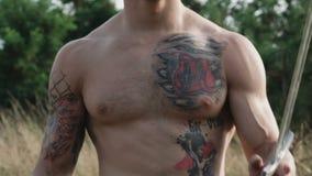 Посмотрите мужского торса с татуировками и шпаги в руке медленно сток-видео